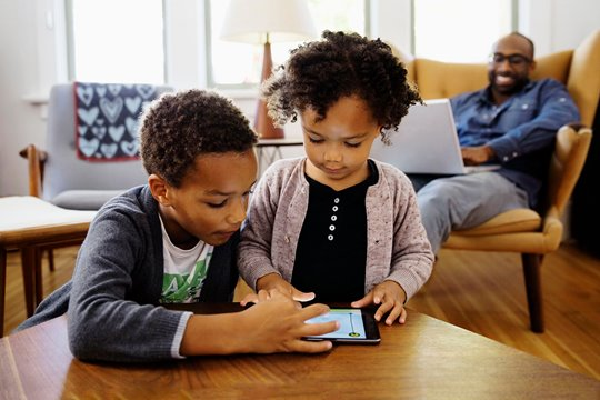 A picture of two kids using a tablet.
